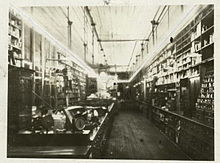 Photograph of a long narrow room taken from one end of the room. Open cabinets are hung on the walls for merchandise; there is a long counter that runs the length of the room. The room is illuminated by a long, glowing glass tube that rings the room and hangs a few feet down from the ceiling.