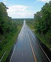 A wet paved road, seen from above. It continues straight ahead into the center of the image, leaving a narrow notch in the foreground to enter a wide, flat landscape in the rear.