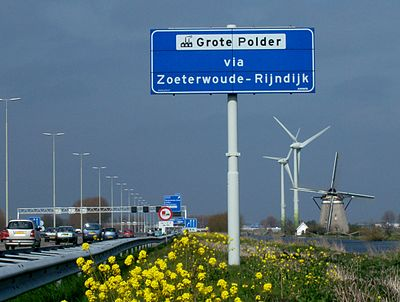 The Netherlands is a heavily developed country. Shown here is a motorway passing by a polder with a drainage windmill, and two wind turbines in the background. Netherlands.jpg