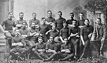 Foto de jogadores e gestão de todos eles da equipe estão sentados ou em pé, em três fileiras, vestindo seu uniforme de jogo e bonés.