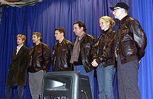 An image of five men and one woman posing in front of a blue curtain. Four of the men and the woman are wearing leather coats and jeans, while the man on the far left is wearing a trench coat and jeans.