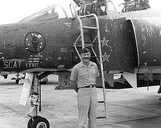 "Robin Olds - Robin Olds beside F-4C Phantom II ""Scat XXVII"", which he flew during his 1966–1967 combat tour as the 8th TFW CO.  Above the ""Scat"" markings, this aircraft also displays the insignia of the 433rd Tactical Fighter Squadron, nicknamed the ""Satan's Angels""."