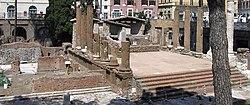 A photograph of Roman ruins in a modern street setting
