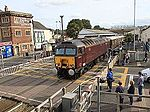 Traffic on Torbay Road comes to a stand as West Coast Railway's 57314 pulls out of Paignton railway station with an excursion train returning north from Kingswear in August 2014
