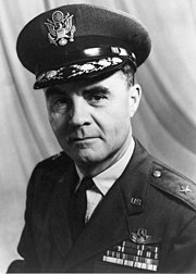 Head and shoulders of man in uniform with peaked cap. He has four rows of ribbons, pilot's wings, and  a star on each shoulder.