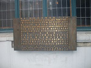 "Artus Court - The memorial board from 1965 which commemorates the 20th anniversary of placing the Polish flag on the Artus Court by ""soldiers of the Polish 1st Armoured Brigade of the defenders of Westerplatte fighting next to the troops of the Red Army's 2nd Belorussian Front under the command of Konstantin Rokossovsky as a symbol of liberation from Nazi occupation and reincorporation into the motherland of the ancient Polish city of Gdańsk""."