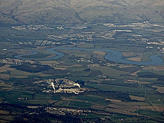 Cambus, Clackmannanshire - Tullibody with Menstrie and Alva at the foot of the Ochils beyond it. The bonded warehouses at Cambus, and Tullibody Inch are nearer the photographic position in the air above Cowie. Meanders on the Forth and the remains of Alloa Swing Bridge from Throsk are also visible.