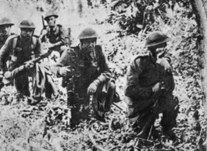 Five soldiers kneel down in woodland.