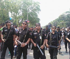 Armed men in black uniforms on a street
