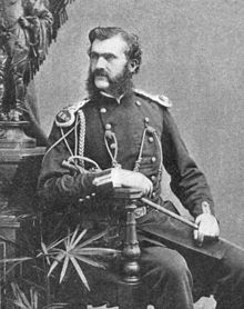 A monochrome photograph portrait of a man with light skin and dark hair, including a bushy muttonchop whiskers and moustache, the man seated, holding a thin sword at rest on his leg, wearing a military uniform decorated with epaulets, braid and buttons