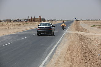 Helmand Province - Locals drive on the new 12-kilometer road built by Afghans partnered with Marine and British engineer mentors. The new road was completed five months ahead of schedule and built entirely by Afghans.
