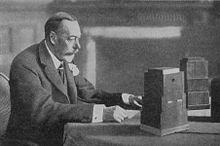 George V assis devant des micros sur une table.