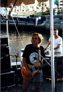 Ruthie Morris standing onstage with a guitar, wearing a black t-shirt with a modified Chuck Taylor All-Stars logo