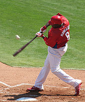 A man in a red baseball jersey, white pinstriped pants, and a red batting helmet swings at a baseball. He is standing in the batter's box on the right-hand side of home plate, and his bat is blurred in motion.