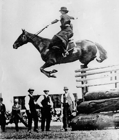 A woman riding sidesaddle clearing a high competition jump in a showground.  There are men beside the jump watching her in admiration of her skill.