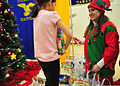 Samantha Patterson, right, a member of the Spouses Association of Kodiak, helps an Ouzinkie student pick out a Christmas bag at the Ouzinkie school during the annual Santa to the Villages visit in Ouzinkie 111207-G-RS249-172.jpg