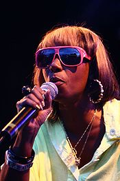 Woman singing into a microphone wearing bright pink sunglasses, large earrings, two small necklaces, and a pale green shirt.