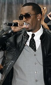 A man wearing a white dress shirt, tie, gray vest, black jacket, and sunglasses, singing into a microphone.
