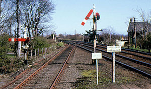 "Railway semaphore signal - Somersault signals at Carrickfergus railway station, showing the distinctive central pivot about which the arm ""somersaults"""