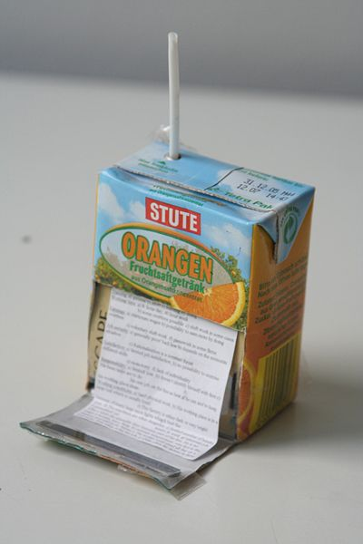 Image depicts an orange juice box with a cheat sheet carefully written and attached to its front.