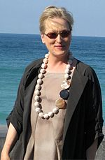 A picture of a brown-haired lady is seen with the ocean in the background. She is wearing a necklace with a gray dress and a black blazer.