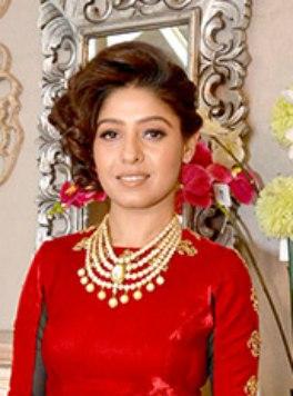 Sundihi Chauhan wearing a red top, looking at the camera half smiling