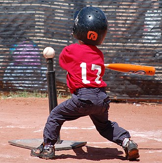 Tee-ball - A tee-ball player swings at a ball resting on the tee.