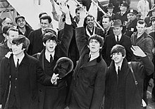 The Beatles are standing in front of the crowd of people at the bottom of an aeroplane staircase.