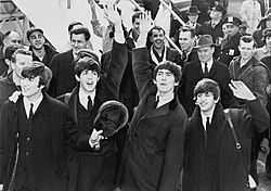 A black-and-white image of Paul McCartney, George Harrison, John Lennon and Ringo Starr waving to fans after arriving in America in 1964. A crowd is visible behind them on the left.