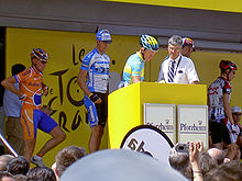 A group of cyclists on a stage near a podium.