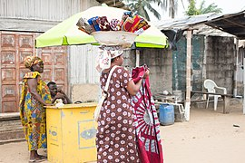Travelling saleswoman carrying African wax prints in the street of Assouinde, Côte d'Ivoire.jpg