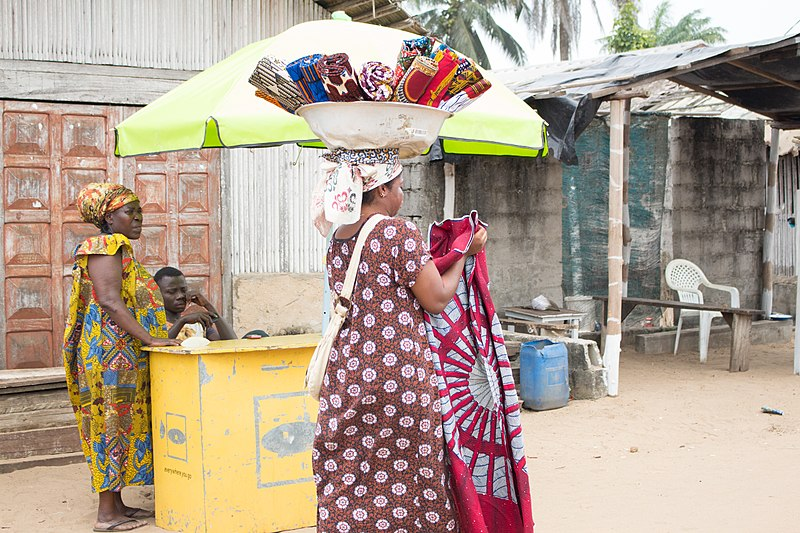 File:Travelling saleswoman carrying African wax prints in the street of Assouinde, Côte d'Ivoire.jpg