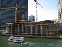 the first few floors of construction of a building from across a river