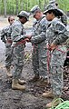 U.S. Army Lt. Col. Mike Hodges, Senior Army Instructor of the Junior Reserve Officers' Training Corps (JROTC) assists a cadet with her rappelling harness, during a JROTC Raider challenge at Joint Base 130513-Z-IB888-006.jpg