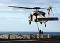 US Navy 051103-N-6125G-071 Aviation Ordnancemen attach ordnance to an MH-60S Seahawk helicopter.jpg
