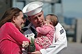 US Navy 060404-N-0946B-002 Electrician's Mate Seaman Brad Murphy admires his new baby girl, with his wife by his side.jpg