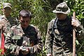 US Navy 070813-N-0989H-186 Cpl. Oscar Garcia, assigned to a U.S. Marine Corps mobile training team, assists a Guatemalan marine with compass reading during a land navigation exercise as part of the U.S. Marine Corps Small Unit.jpg