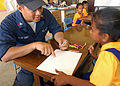 US Navy 070829-N-9421C-049 Machinist's Mate 2nd Class Brian Delos Trinos draws a picture of a ship for a local student during a community relations project at Delap Elementary School in support of the Pacific Partnership missio.jpg