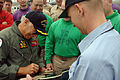 US Navy 080128-N-8923M-035 Recording artist Jimmy Buffett autographs a Sailor's guitar on the flight deck of the aircraft carrier USS Harry S. Truman (CVN 75) during a recent port visit in the Middle East.jpg