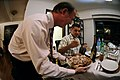 US Navy 081127-N-8546L-113 Meals in the Home volunteer host, Tim Sullivan, holds a plate of freshly cut turkey as Storekeeper 2nd Class Jose Betancourtcantu forks a few slices onto his plate.jpg