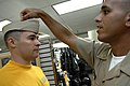 US Navy 090713-N-9818V-064 Chief Machinist's Mate Jordan Rosado helps Aviation Warfare Systems Operator 1st Class William Frost, Reserve Sailor of the Year, get fitted for his new uniform.jpg
