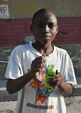 Mechanically powered flashlight - A Haitian boy turns the crank on his crank-powered flashlight radio. Mechanically powered flashlights were distributed by aid organizations to survivors of the 2010 Haiti earthquake since electric power was lost for a long period.