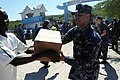 US Navy 100125-N-5700G-410 A Sailor assigned to the amphibious assault ship USS Nassau (LHA 4) distributes food at a humanitarian aid distribution point in Saint Marc, Haiti.jpg