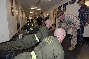 Officer Candidate School (United States Navy) - A USMC Drill Instructor (right, wearing a campaign cover) offers motivation and critiques an Indoctrination Candidate's push up form.