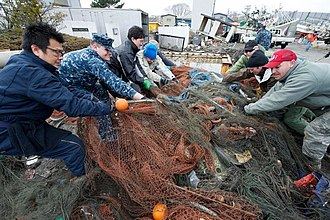 U.S. sailors assist locals and French volunteers to clear the harbor in Hachinohe US Navy 110321-N-9436A-099 Cryptologic Technician (Collection) 2nd Class Gregory Allison, left center, from Glen Burnie, Md.jpg