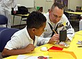 US Navy 110830-N-NT881-076 Fire Control Technician 1st Class, Shane Adkins assists a Taft Elementary School student learn the principles of buoyanc.jpg