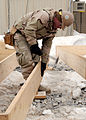 US Navy 120202-N-SD610-001 A Sailor attaches a mud sill to a joist during the construction of wooden flooring for installation in an Alaska tent.jpg