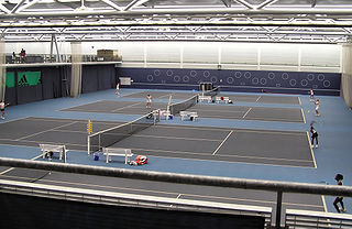 Tennis court venue where the sport of tennis is played. It is a firm rectangular surface with a low net stretched across the center. The same surface can be used to play both doubles and singles matches