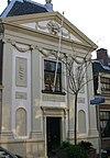 foto van Hof van Brouckhoven, zestien woningen met natuurstenen versierde poort waarboven regentenkamer. Achtergevel aan de Lange Schoolstraat