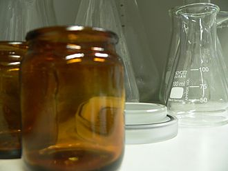 Laboratory glassware - Brown glass jars with some clear lab glassware in the background